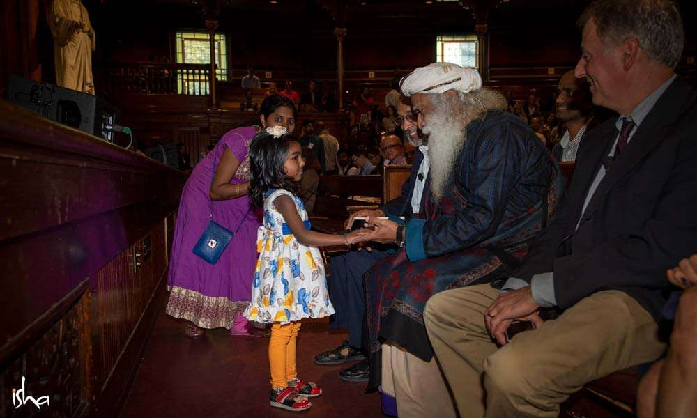One of the young members of the audience greets Sadhguru.